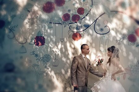the groom looks at the bride against the wall decorated with flowers. A man admires a woman. Family Day concept, Valentines Day, wedding Stock Photo