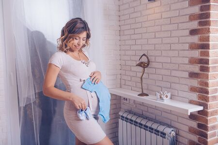 a pregnant woman in a light dress and stockings considers childrens clothes. Healthy lifestyle concept, IVF fashion for pregnant women, children