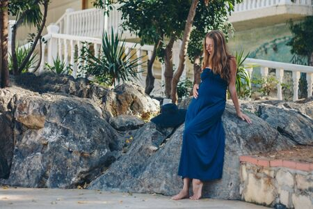 a pregnant woman sits on the stone of a historic building. Tourist on an excursion. Girl on vacation Banco de Imagens