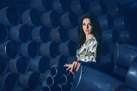 model business concept, heavy industry, building materials, beautiful brunette with bright red manicure, in dress and shoes posing among metal pipes. A woman in beautiful clothes, standing in the warehouse of metals Reklamní fotografie