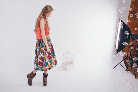 advertising clothes and interior items: a girl in a colored skirt and shoes on a white background next to the birdcage. Mannequin.