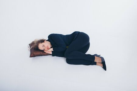 businesswoman in a business suit sleeping on the floor on a pillow on a white background. The concept of business everyday life, vacation, work break