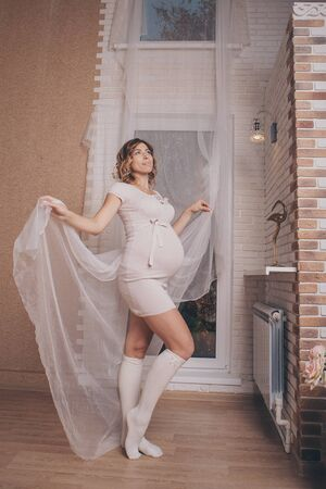 a pregnant woman in a light dress and stockings stands thoughtfully at the window, playing with curtains. The concept of a healthy lifestyle, IVF 写真素材