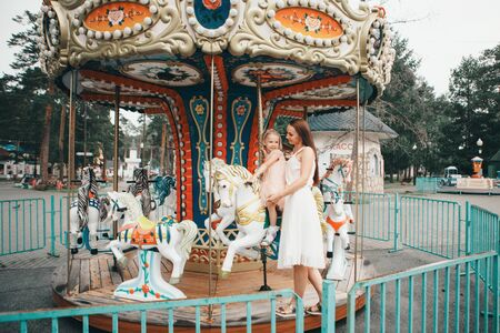 a little girl with her mother riding in the Park on a toy horse on the carousel. Entertainment industry concept, family day, childrens parks, playgrounds