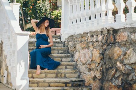 a pregnant woman sits on the stone steps of a historic building. Tourist on an excursion. Girl on vacation Reklamní fotografie