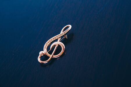 Gold violin on a dark background. embellishment: brooch. copy space. The concept of musical symbols, isolated objects, jewelry work, jewelry