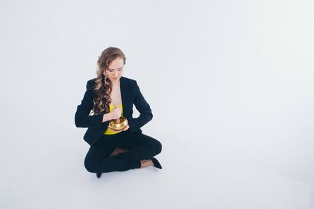 businesswoman meditating. Preparation of a potion on a white background. Singing bowl with Buddhist mantra in womans hand in a suit 写真素材