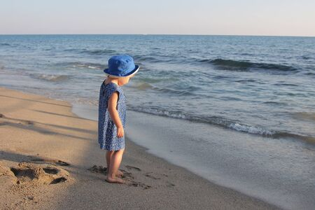 a little girl in a dress and hat walking on a sandy beach. The child plays on the shore. The concept of recreation, tourism, childhood Reklamní fotografie
