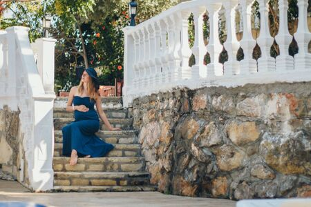 a pregnant woman sits on the stone steps of a historic building. Tourist on an excursion. Girl on vacation 스톡 콘텐츠