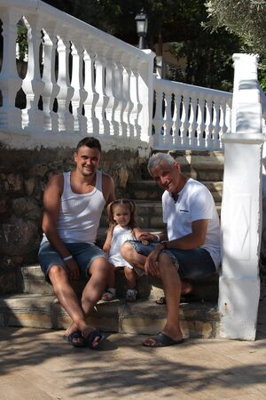 men and child sitting on the stone steps of a historic building. Tourists on an excursion. Family on vacation Banco de Imagens