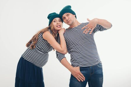 the concept of domestic violence, manifestations of emotions, sea travel. Pregnant woman mocks the guy: pulls the face. Couple in Navy suits on white background