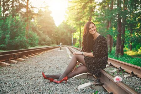a beautiful brunette in a black dress and red shoes sits on the rails. Woman advertises accessories, cosmetics, makeup, clothes Stok Fotoğraf