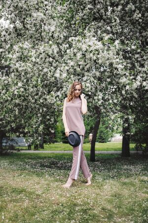 girl walking in the Park among the flowering trees. Spring mood-a woman in nature