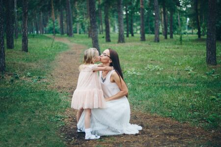 the concept of walking, healthy lifestyle. A woman and a girl walking hand in hand in the woods. Mom and daughter in white dresses
