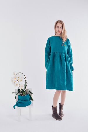 advertising clothes: a girl in a blue dress on a white background. model next decorative element of the interior: a flower in a pot.