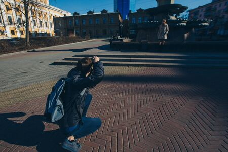the photographer takes a beautiful model on the street by the fountain. Girl advertises clothes. Photo and video advertising