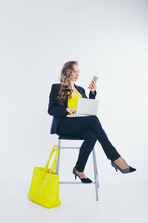 office concept, business plan, fashion-businesswoman in black and yellow suit talking on the phone and working on a laptop. big yellow bag. Beautiful woman sitting on chair on white background Stock Photo