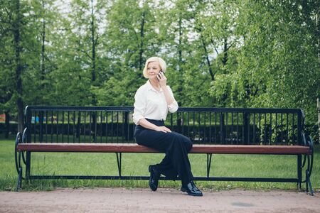 entrepreneur talking on the phone in the Park. Blonde hair Bob works outside. businesswoman with smartphone Reklamní fotografie
