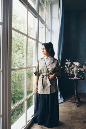 beautiful Asian woman with a hairstyle in Japanese style and a kimono at the window on the background of the home interior Stok Fotoğraf
