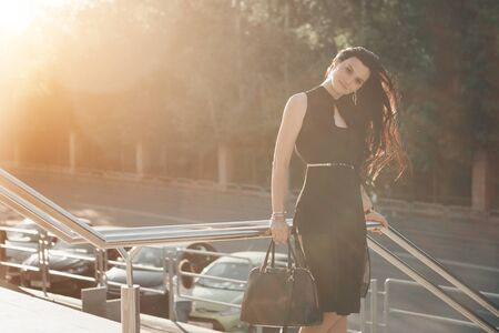 beautiful brunette in a black dress with a bag walking down the street in the light. Woman advertises accessories, cosmetics, makeup