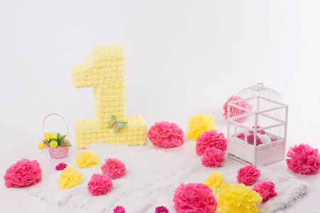 the concept of a festive interior, attributes of a holiday, decorative elements: number one, flowers, a cage for birds on a white background. Pink and yellow Reklamní fotografie