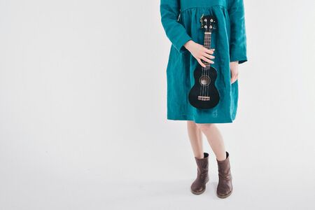 beautiful girl in blue dress with small guitar in hands on white background. The concept of advertising musical instruments, fashion, symbols Reklamní fotografie