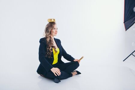 businesswoman meditating. Preparation of a potion on a white background. Singing bowl with Buddhist mantra in womans hand in a suit Фото со стока