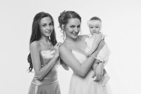 wedding fashion concept for women of all ages. A group of women in long evening dresses on a white background