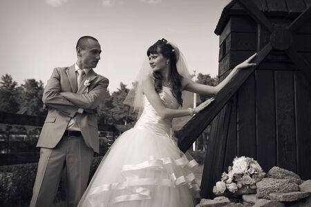 the concept of a romantic walk. A loving couple holding hands. Bride and groom at the little mill. Concept of household, production of flour, bread, interior, wedding fashion