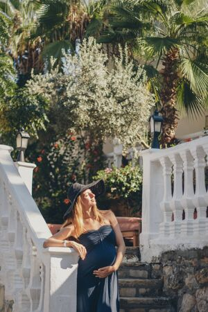 a pregnant woman sits on the stone steps of a historic building. Tourist on an excursion. Girl on vacation Banco de Imagens