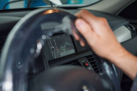the interior of the car. the man behind the wheel looks out the window. Demonstration of steering wheel, seats, control panel, business class car Stock Photo