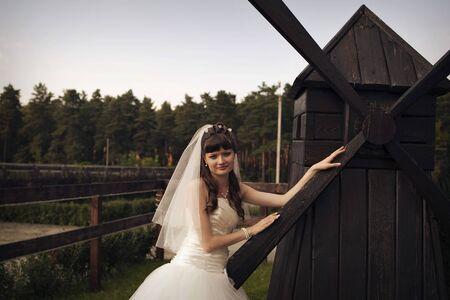 the concept of a romantic walk. Bride at the little mill. Concept of household, production of flour, bread, interior, wedding fashion