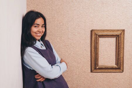 beautiful cute girl smiling near the empty frame. Copy space. The concept of empty space for advertising, models for demonstration of texts
