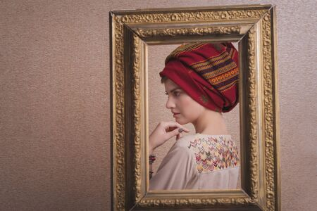 beautiful sweet girl in turban in frame. Copy space. The concept of empty space for advertising, models for the demonstration of texts, painting, art