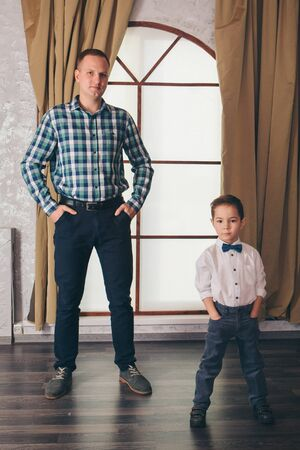 two men in identical poses. Father and son. Business development concept, demonstration of strength, continuity
