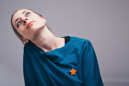 the concept of sewing accessories: brooch in the shape of a star. portrait of a beautiful woman in blue clothes Imagens