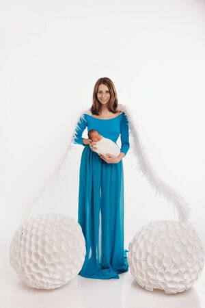 A girl in a blue dress with angel wings holding a newborn baby on a white background. An angel-woman and child have big white balls. The concept of Christmas, mystical creatures, Halloween