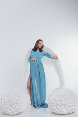 A pregnant girl in a blue dress with angel wings on a white background. An angel-woman have big white balls. The concept of Christmas, mystical creatures, Halloween, new year suit