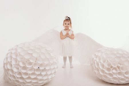 A girl in a white dress with angel wings holding on a white background. An angel-child have big white balls. The concept of Christmas, mystical creatures, Halloween Zdjęcie Seryjne