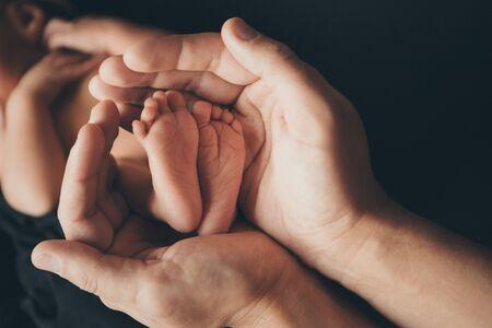 Newborn Babys feet.Mother holding newborn baby legs,legs massage Stock Photo