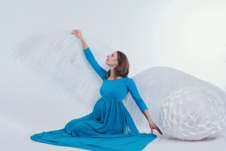 A pregnant girl in a blue dress with angel wings sitting on a white background. An angel-woman have big white balls. The concept of Christmas, mystical creatures, Halloween 스톡 콘텐츠