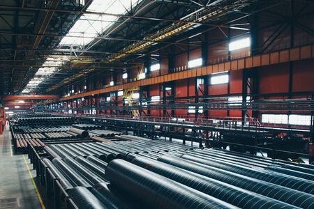 heavy industry concept, construction machinery - long metal pipes inside a large room. Building materials in the hangar