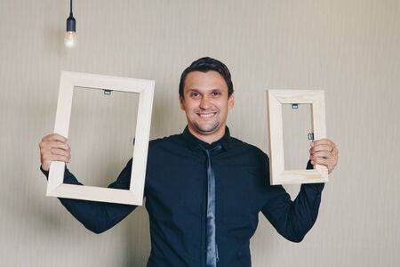 beautiful man smiling near the empty frame. Copy space. The concept of empty space for advertising, models for demonstration of texts Фото со стока