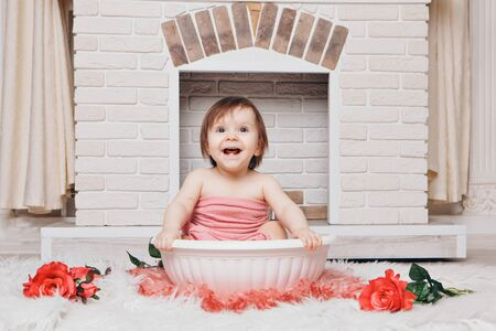 A little girl is bathing in a bath with flowers by the fireplace. A child washes in a basin among red rosers. concept of childhood, health care, IVF, hygiene, aroma therapy