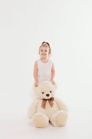 a small child with toy Taddy bear. Girl playing on white background. Concept of gift, childhood