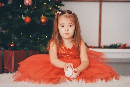 small girl in red clothes with snow ball in hand under the Christmas tree. the concept of celebrating Christmas ,midnight, new year,