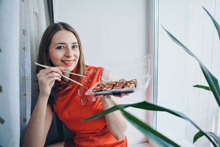 blue-eyed Caucasian girl in traditional Chinese dress eating sushi sticks. Blonde in Japanese culture. concept of healthy food, Oriental cuisine