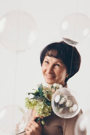 beautiful girl holding flowers on white background. March 8: woman among flowers. the concept of congratulations, women's holidays, natural make up