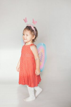 A little girl with colorful wings. A child in a fairy costume. Christmas concept, mystical creatures, Halloween, carnival, costume party