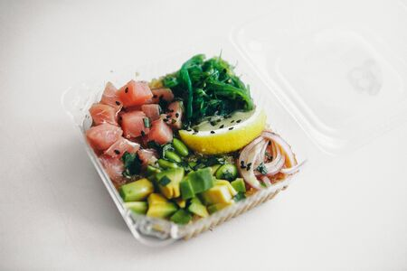 Japanese cuisine: fish, lemon, onion, avocado in a plastic container. Advertising concept of traditional Oriental cuisine